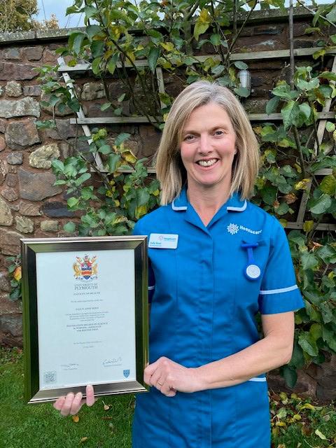 A Hospiscare nurse holding a graduation certificate