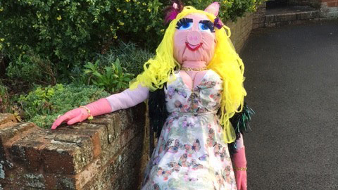 A scarecrow of Miss Piggy sitting on a chair