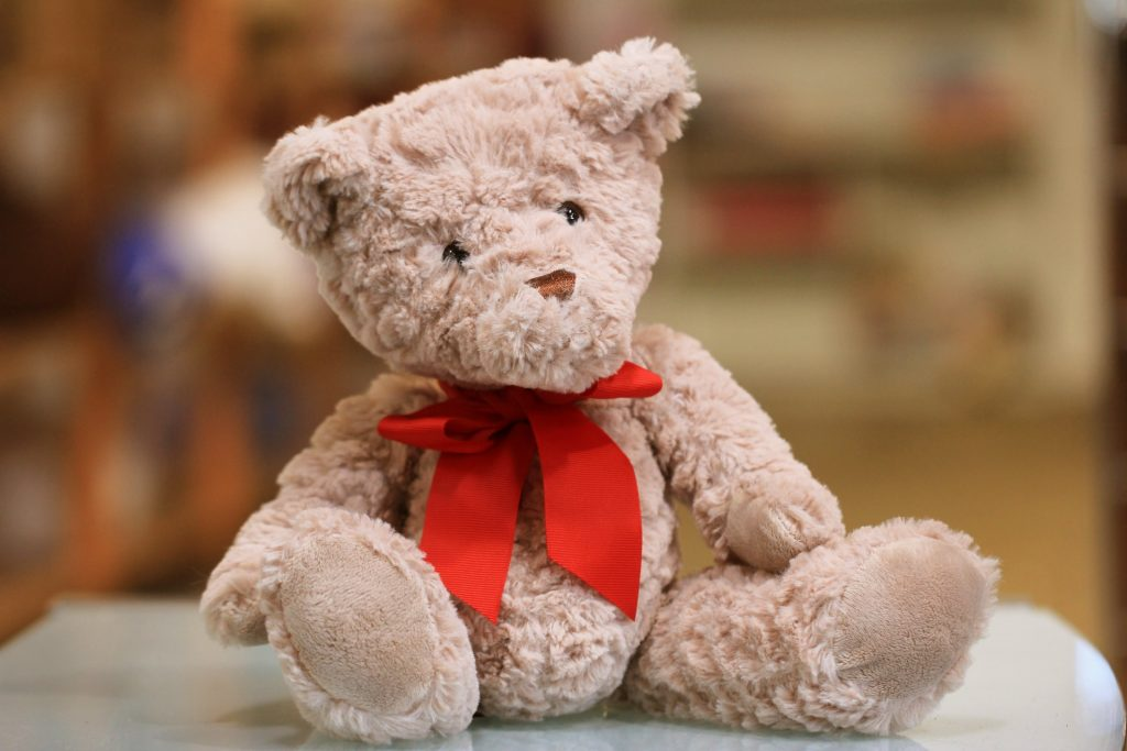 A beige teddy bear with a red bow