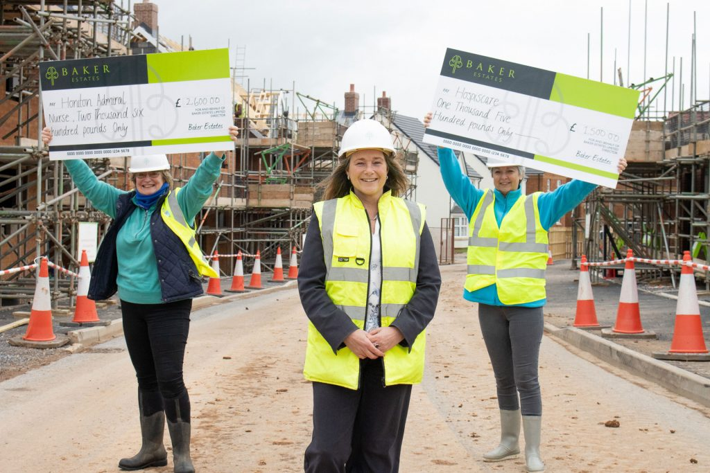 Three women on a building site holding up 2 big cheques
