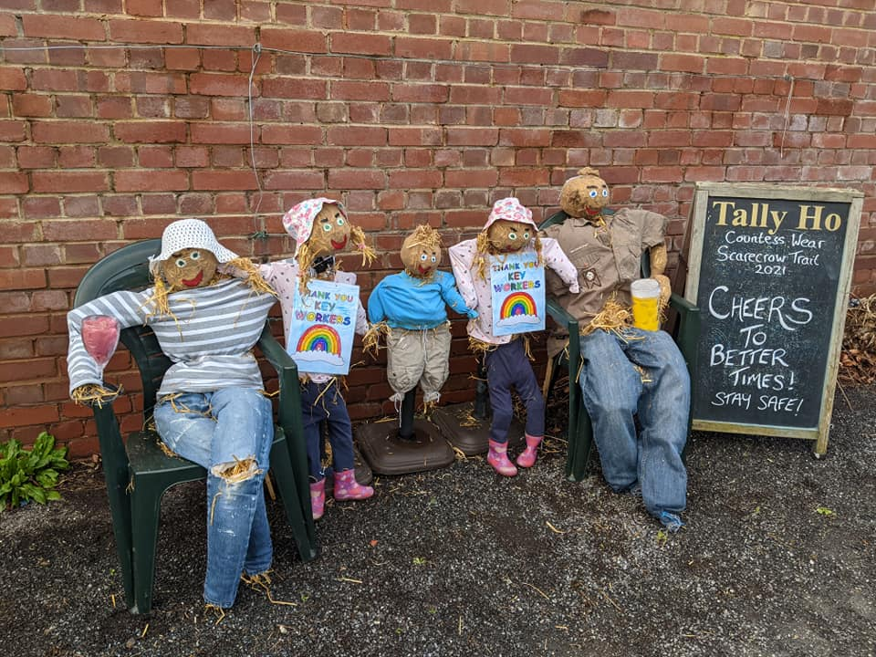 A family of scarecrows sat on a bench