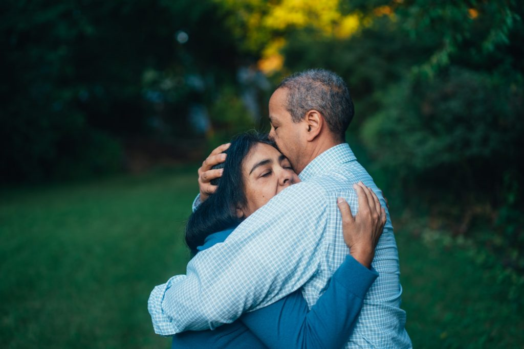 A woman and man hugging in a garden