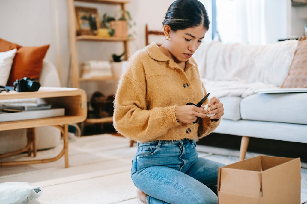A woman kneeling next to an open cardboard box