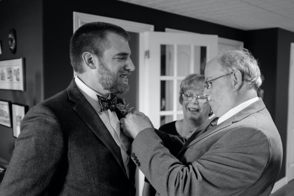 A man on his wedding day with his parents