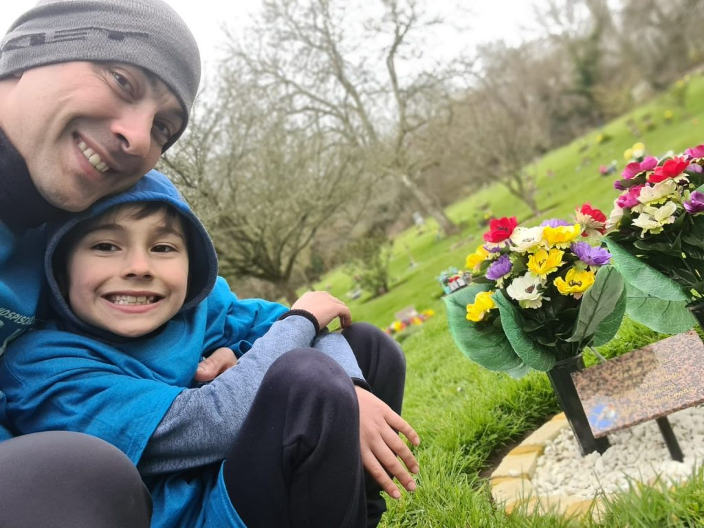 A man and young boy next to a grave with flowers