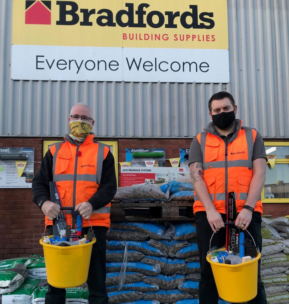Two men holding tool buckets at Bradfords Building Supplies
