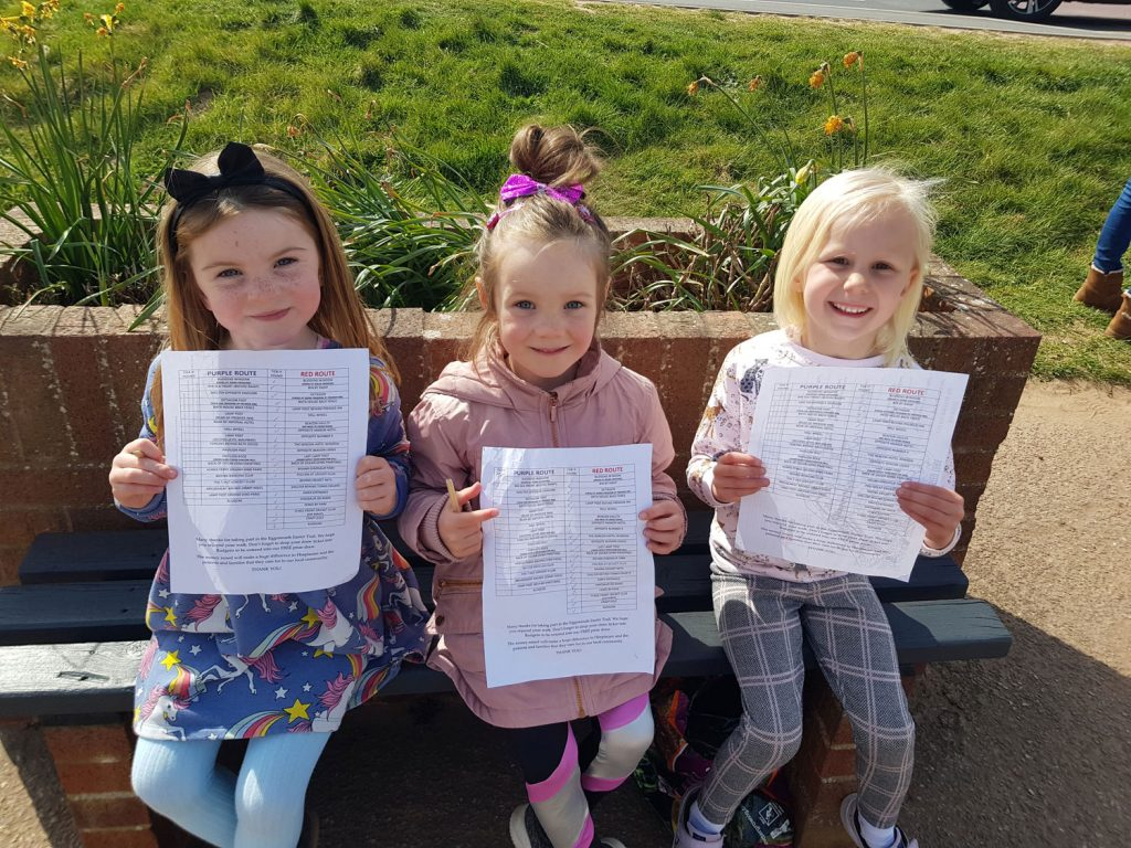 Three young girls holding white lists