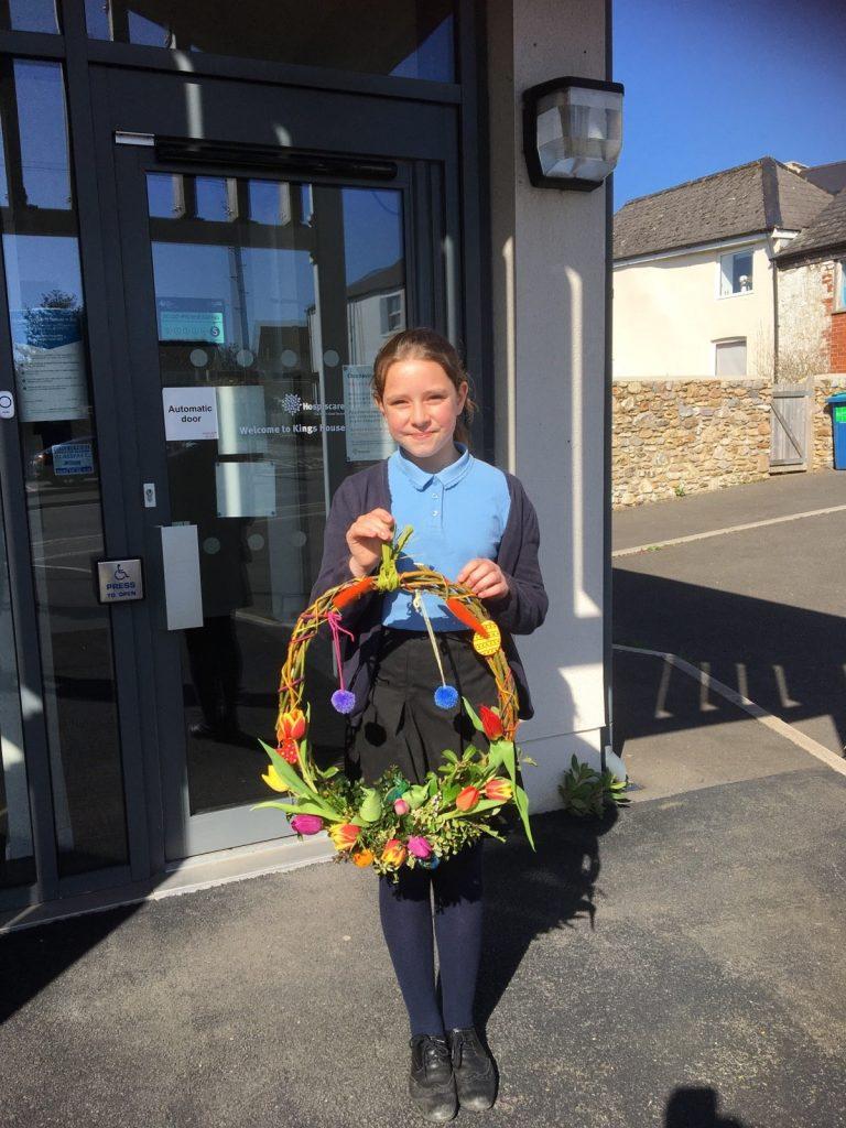 A girl in school uniform holding a handmade wreath