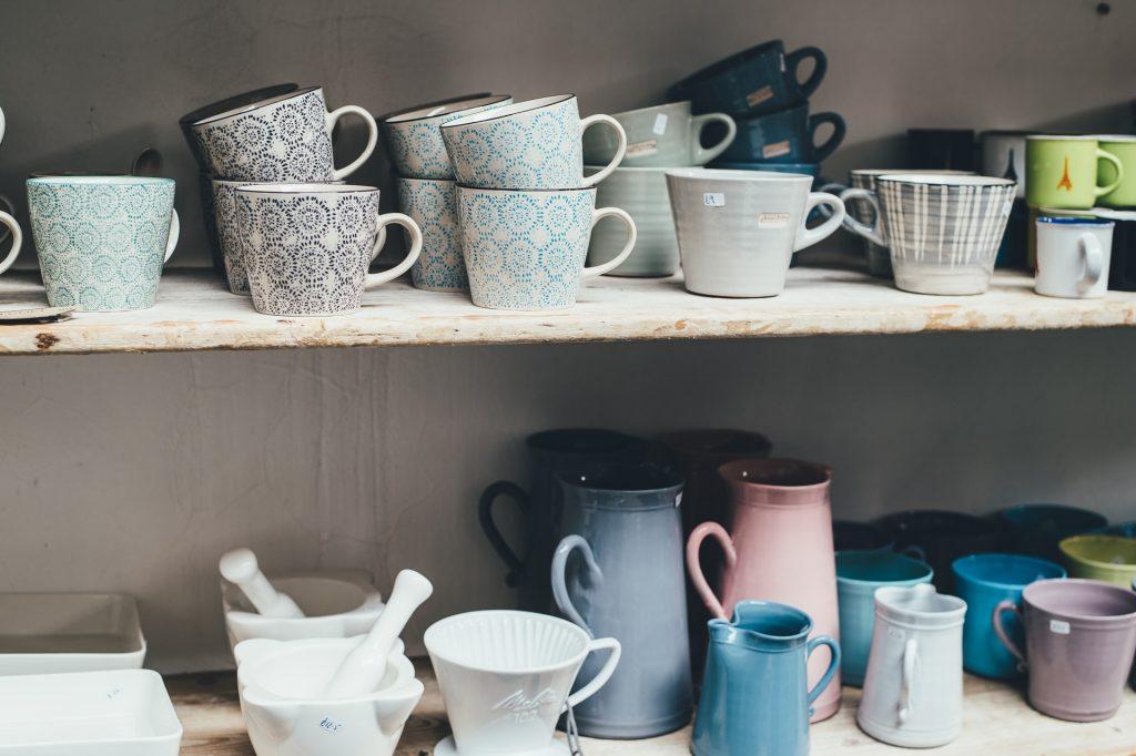 A shelf full of cups, mugs and jugs