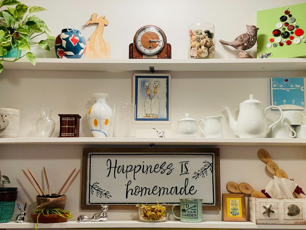 Shelves in a kitchen with a sign saying 'Happiness is homemade'