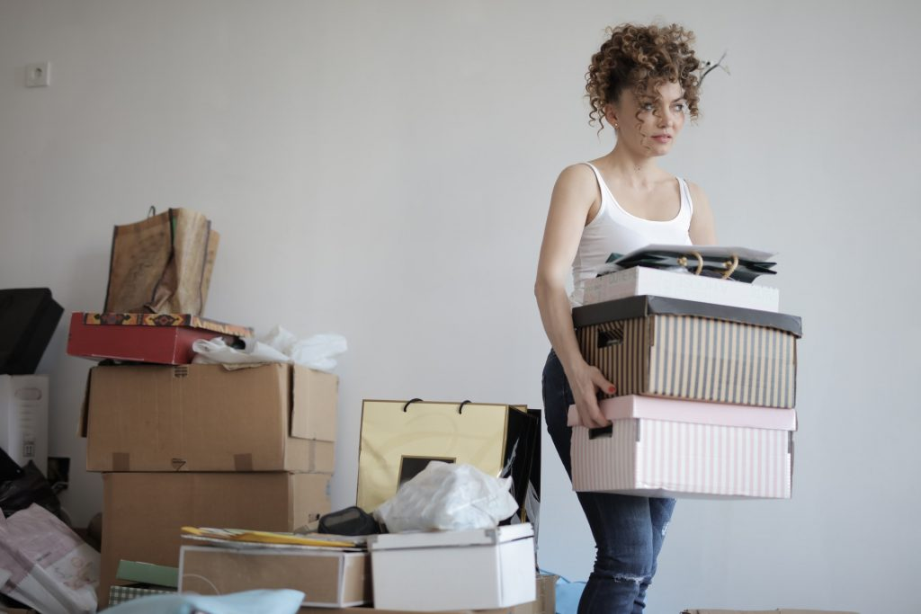 A woman carrying a stack of boxes