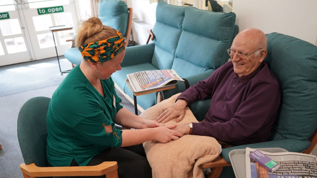 An elderly man having a hand massage from a woman