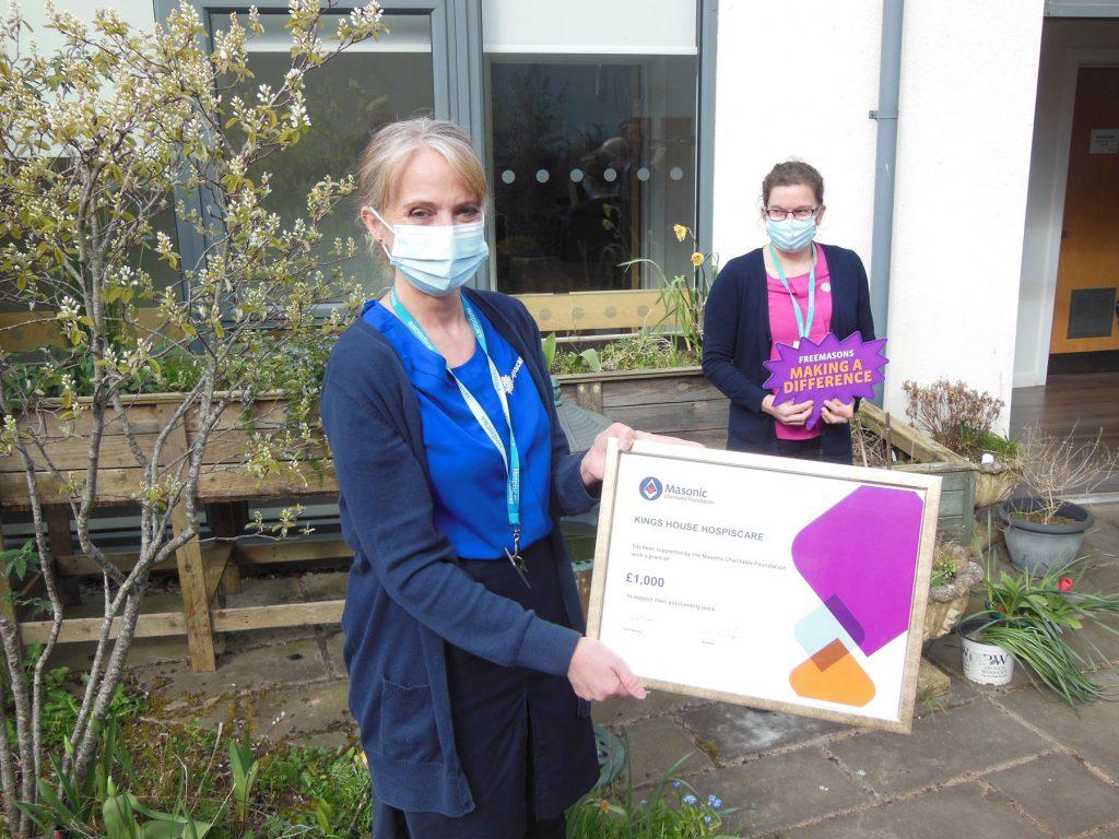 A nurse holding a large cheque in a garden