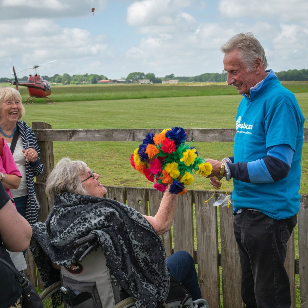 An elderly man presenting a bunch of flowers to a woman in a wheelchair