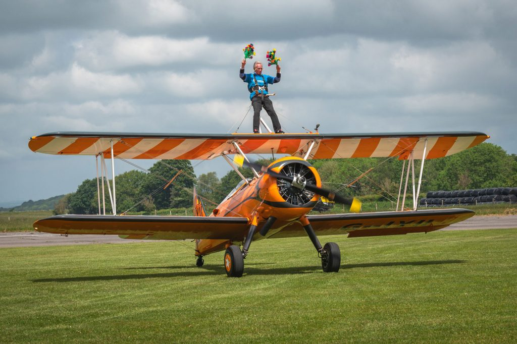 A man strapped to the wings of a bi-plane holding 2 bunches of flowers