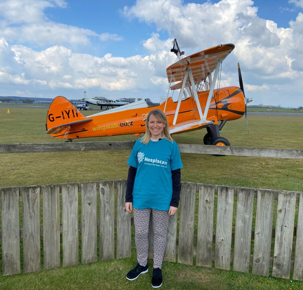 A woman standing in front of a yellow bi-plane