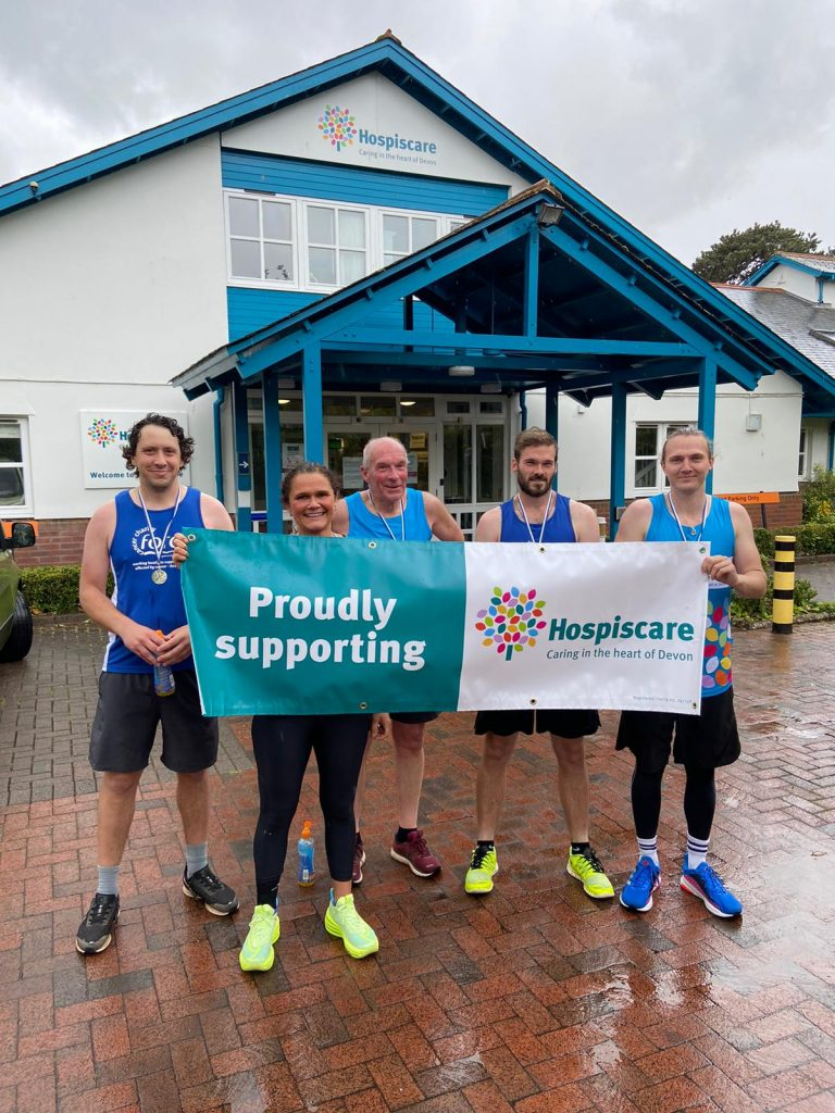 A group of people in running gear holding a Hospiscare banner outside in the rain