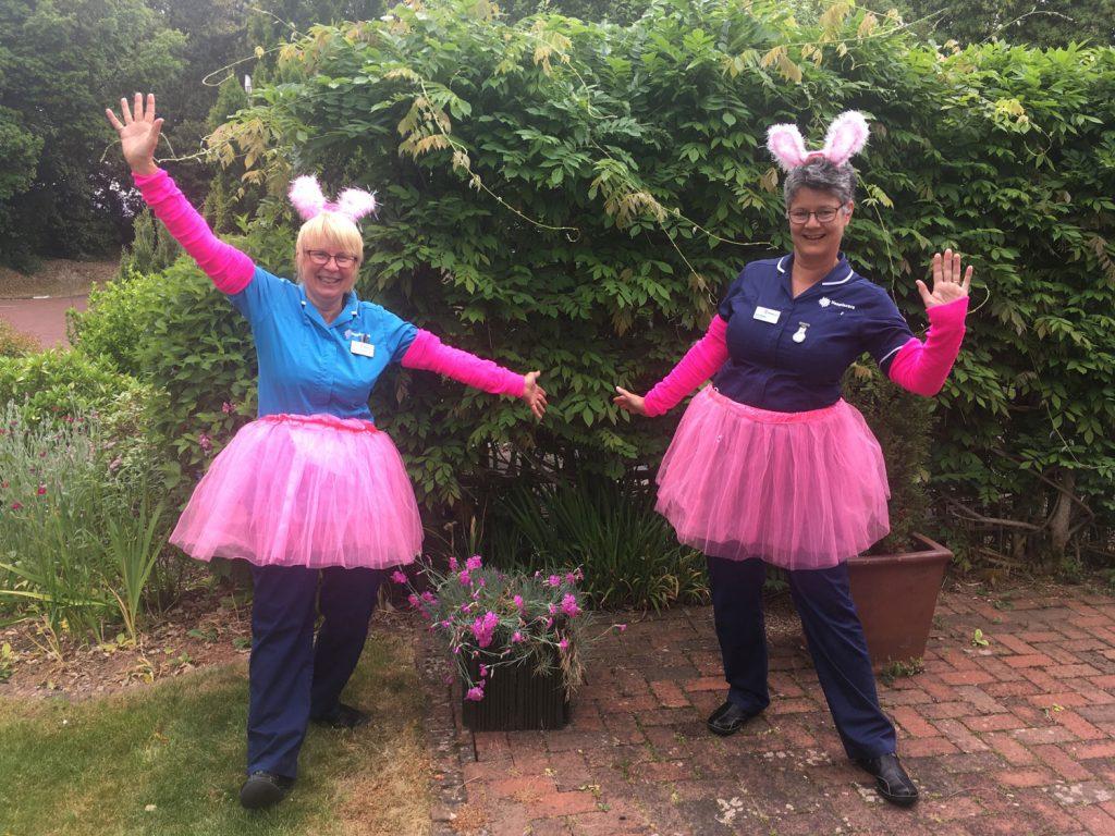 Two nurses in a 'ta da' pose wearing pink tutus