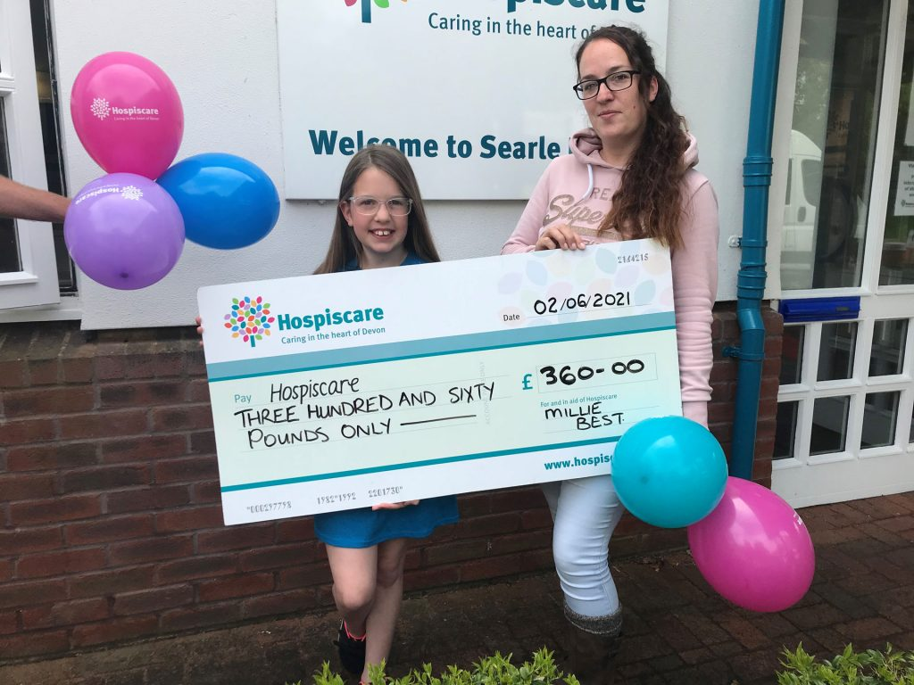A girl and a woman holding balloons and a big cheque for Hospiscare