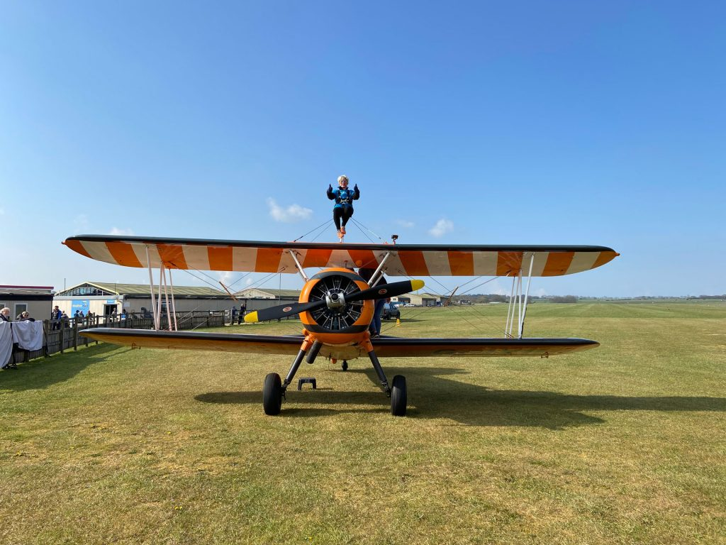 A woman strapped to the wings of a bi-plane