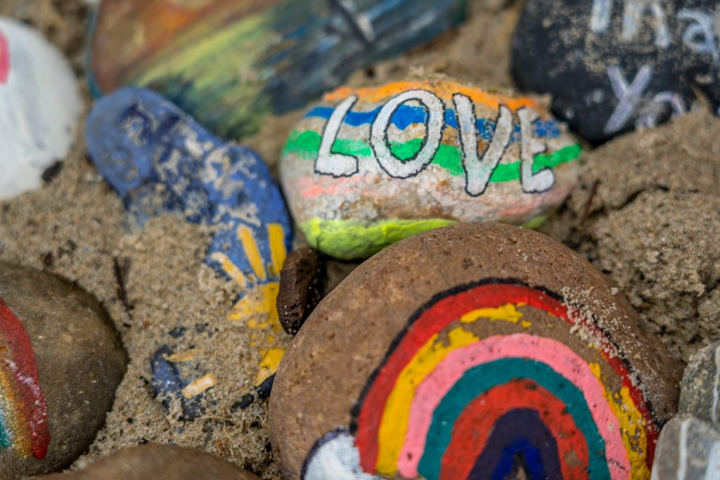 A collection of painted pebbles on sand