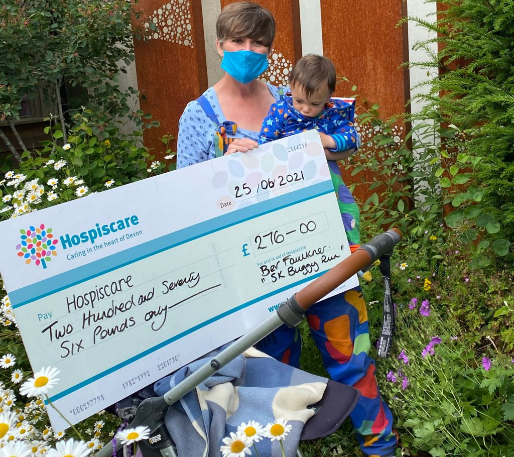 A woman holding a large cheque and a toddler