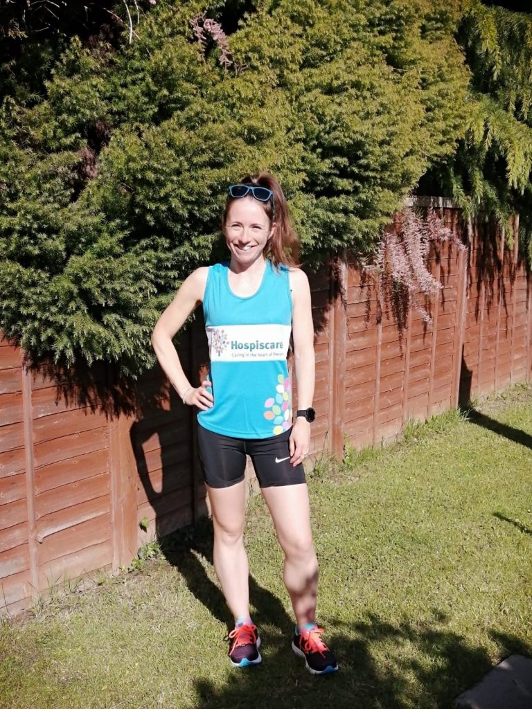 A woman standing outside wearing a Hospiscare running vest