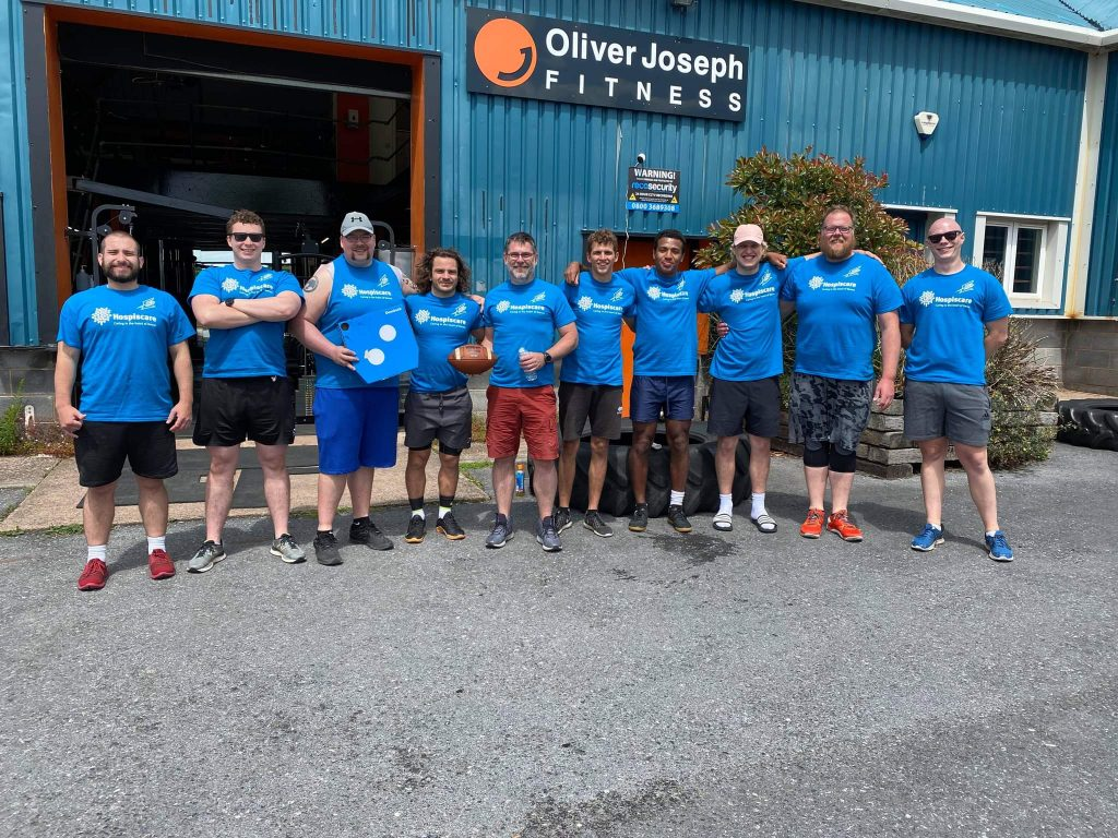 A group of men outside a gym wearing Hospiscare t-shirts