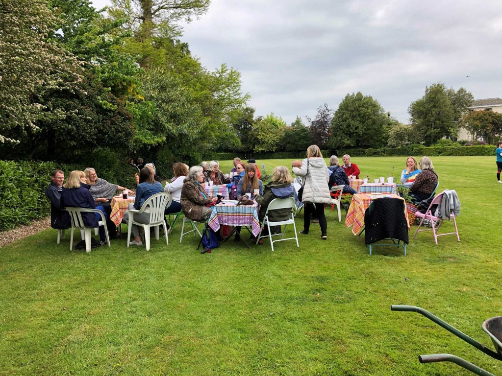 A group of people sat at tables in a field