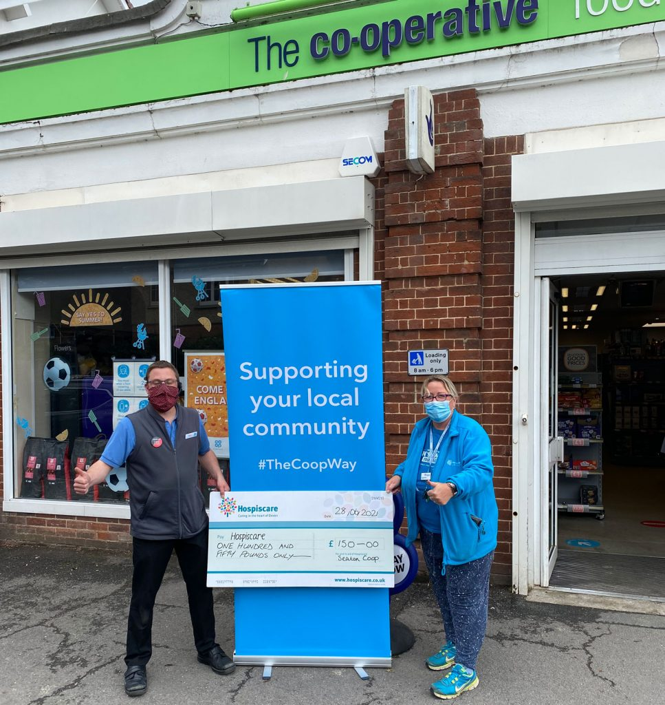 Two people wearing masks holding a big cheque outside coop