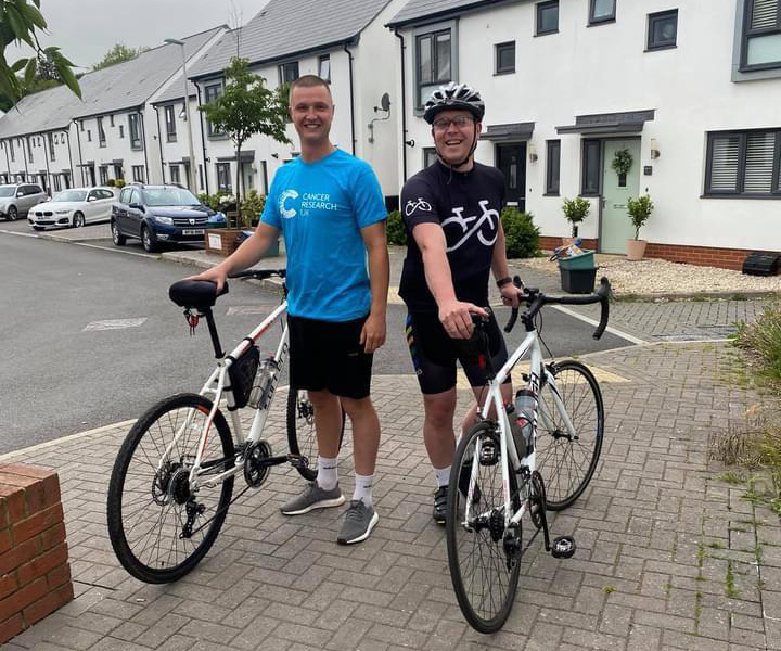 Two men with bicycles outside a housing development