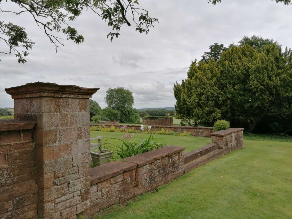A garden with a stone wall