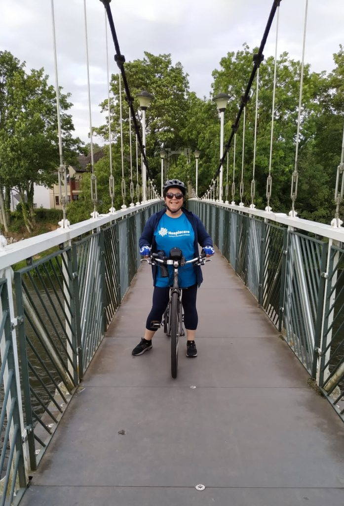 A woman astride a bicycle on a pedestrian bridge