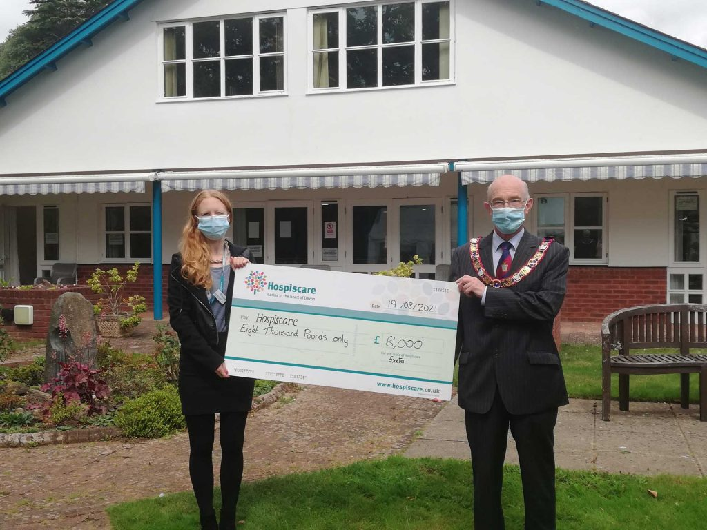 A woman and a man holding a big cheque wearing masks