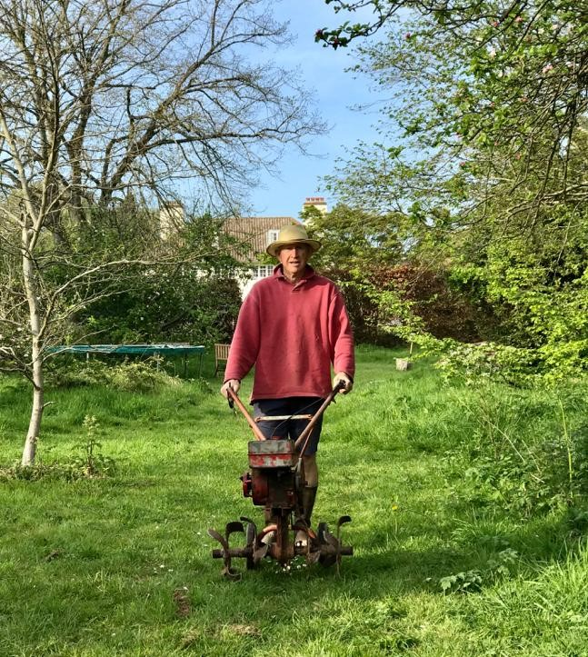 A man with an old-fashioned mower in a garden