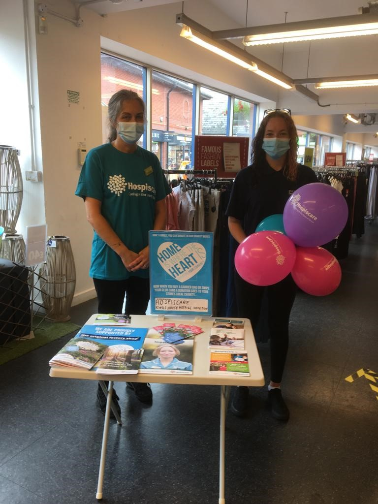 Two people wearing Hospiscare t-shirts in a shop