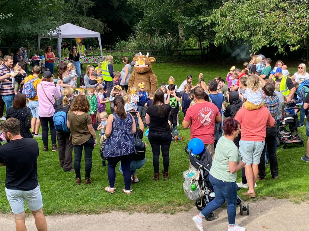 A group of people clustered around a Gruffalo