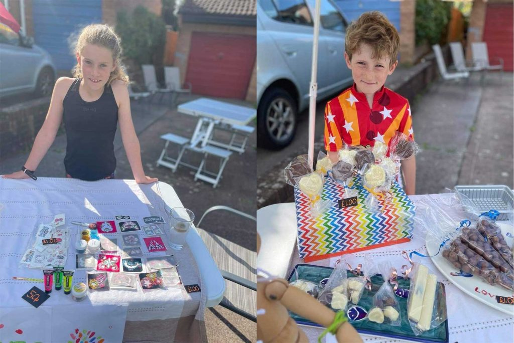 A young girl and boy at a table top sale