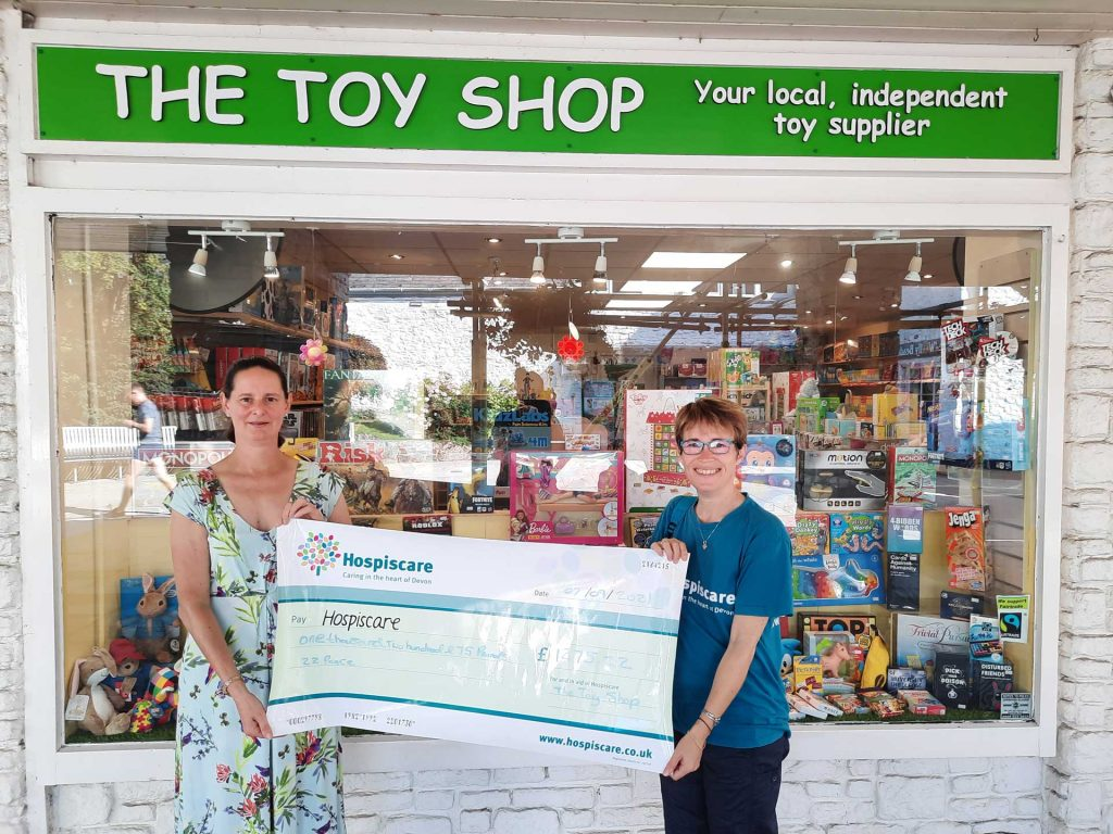 Two women holding a big cheque outside a toy shop