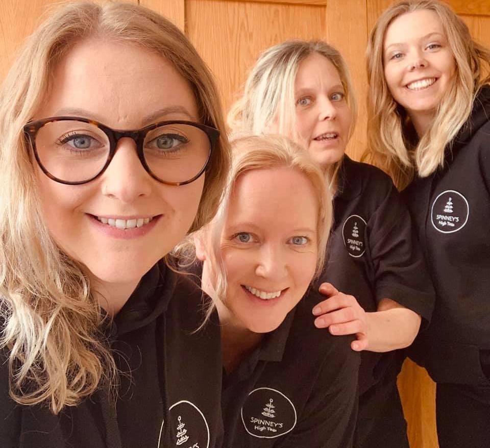 Five women wearing dark hoodies