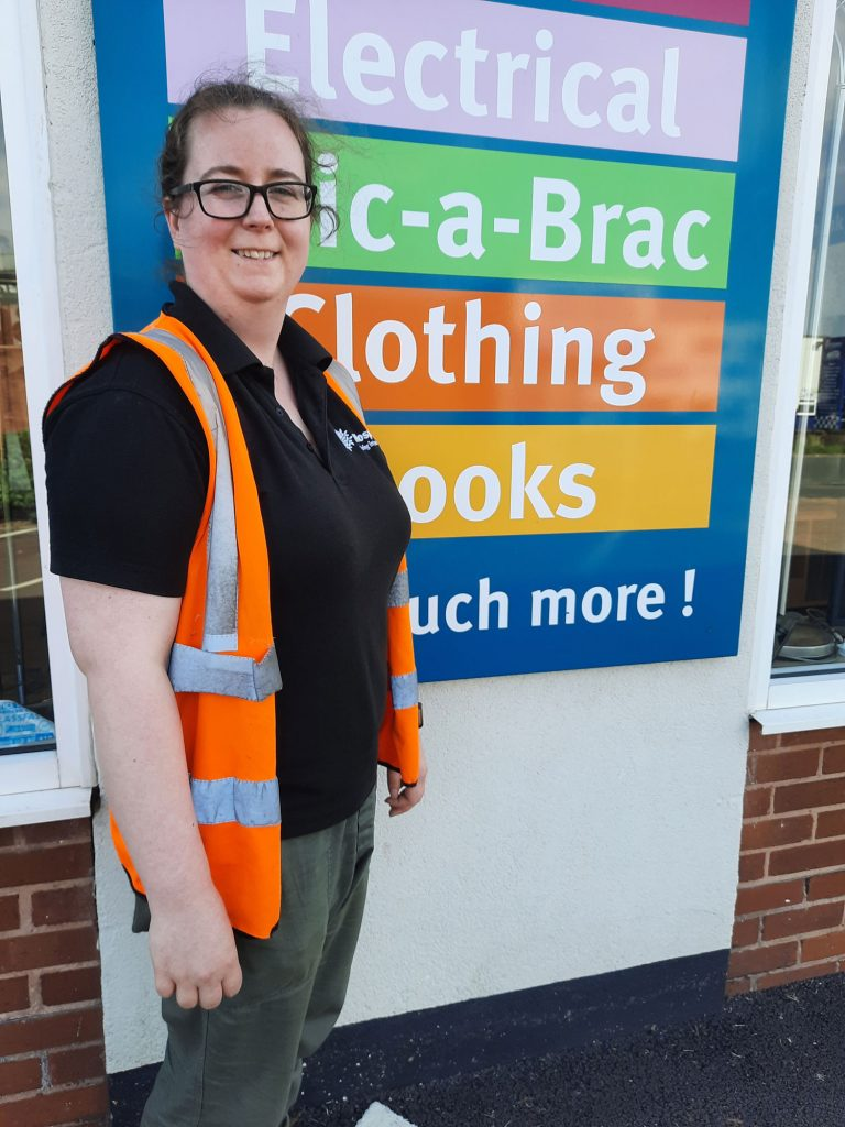 A woman wearing a high vis standing in front of a sign