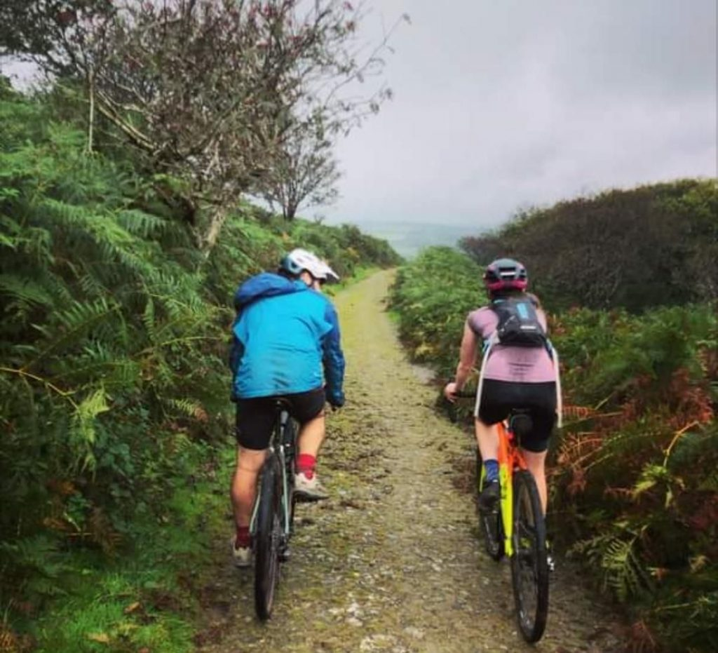 A man and woman cycling captured from behind